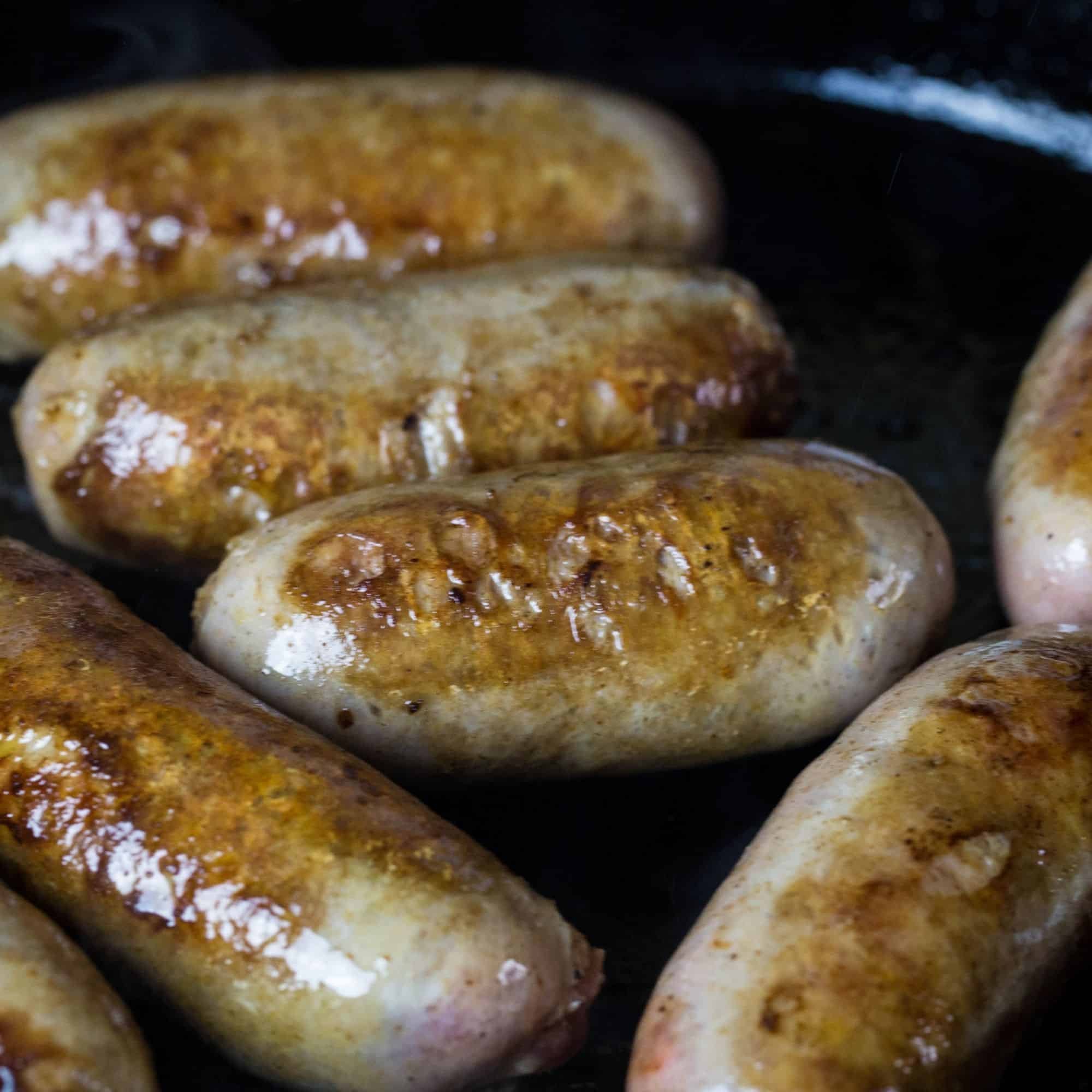 Bangers, Irish sausage being browned on a cast iron skillet.