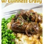Delicious Irish Bangers with caramelized onions and Guinness gravy over mashed potatoes and green peas.