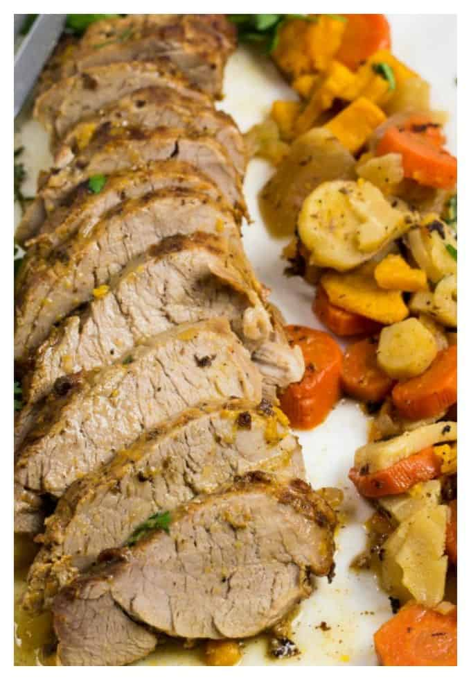 sliced pork tenderloin with sweet potatoes, white potatoes, and carrots on a long white platter.