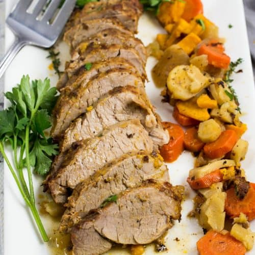 Sliced pork tenderloin with root veggies on a white platter