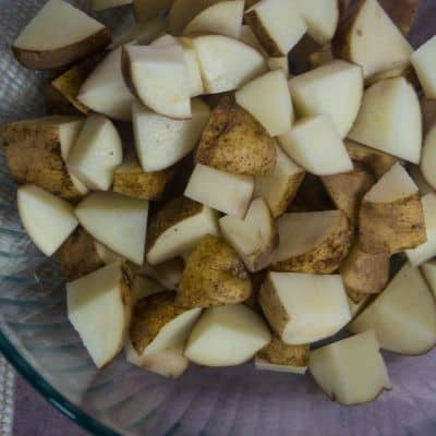 cubed potatoes in a glass bowl ready to be seasoned with spices and olive oil to make crispy roasted potates