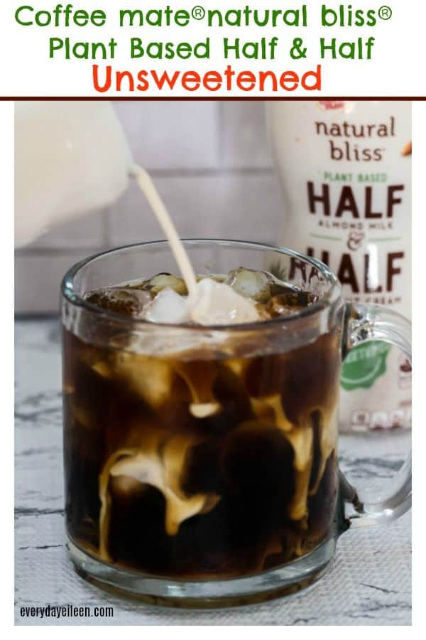 An iced coffee in a glass coffee mug with natural bliss half and half being poured into the glass.