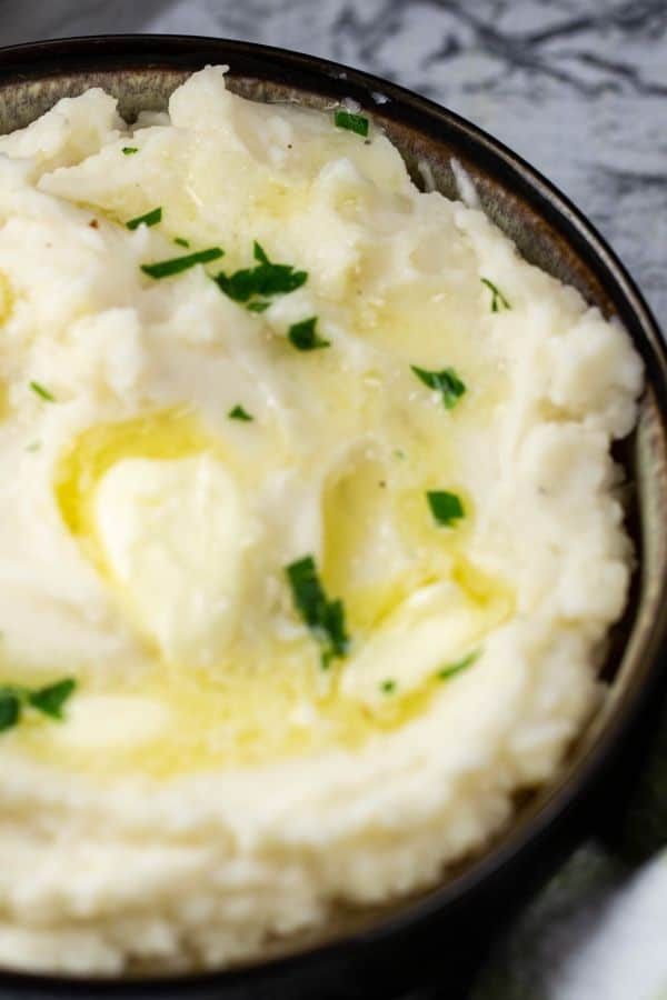 Instant pot mashed potatoes with melted butter and sprinkled fresh parsley on the potatoes.