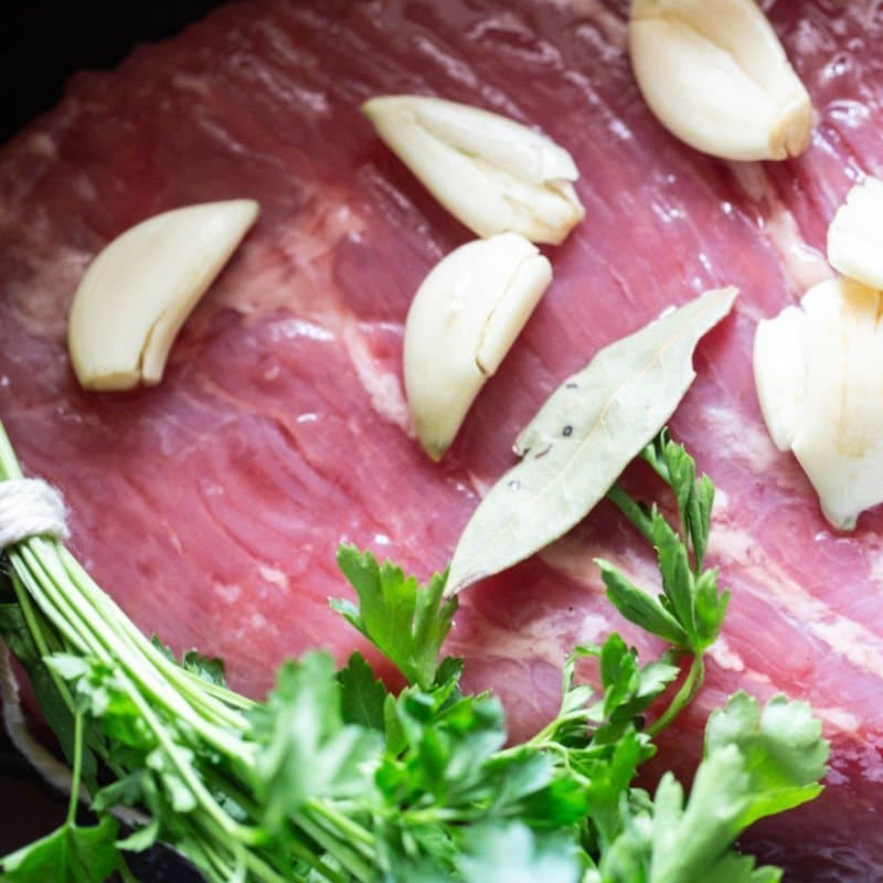 Corned beef with spices, onion, and parsley in a slow cooker beginning the prep of corned beef and cabbage.