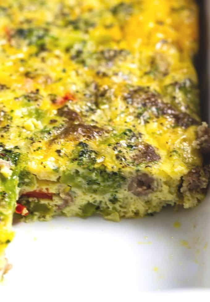 A slice of an egg baked with broccoli, cheese, and sausage