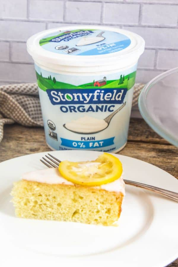 A slice of lemon yogurt cake with a candied lemon piece on top with a carton of Stonyfield plain yogurt behind it.