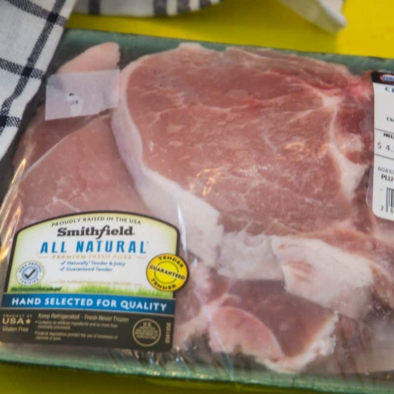 Smithfield pork chops in its packaging on a yellow platter.