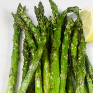 Tender asparagus on a white plate that has been grilled with a lemon wedge on the side