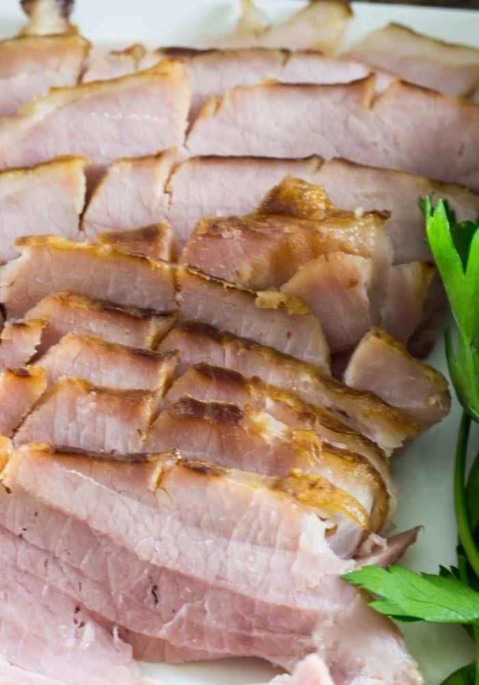 Sliced honey glazed ham on a white platter.