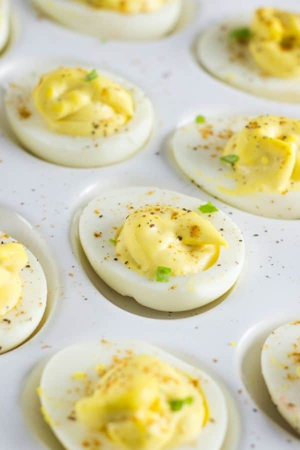 horseradish deviled eggs on an egg platter with smoked paprika sprinkled on the eggs