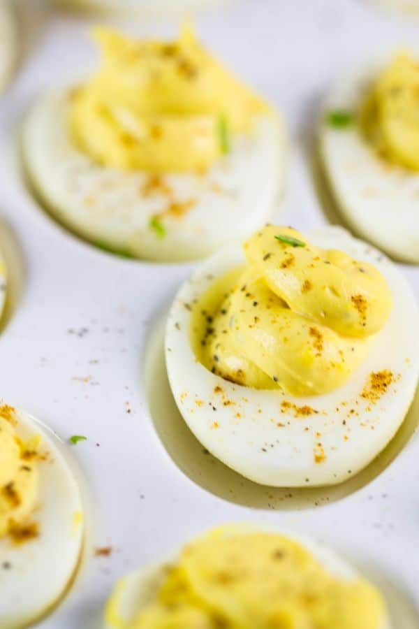 A tray of deviled eggs that are filled with a horseradish cream.