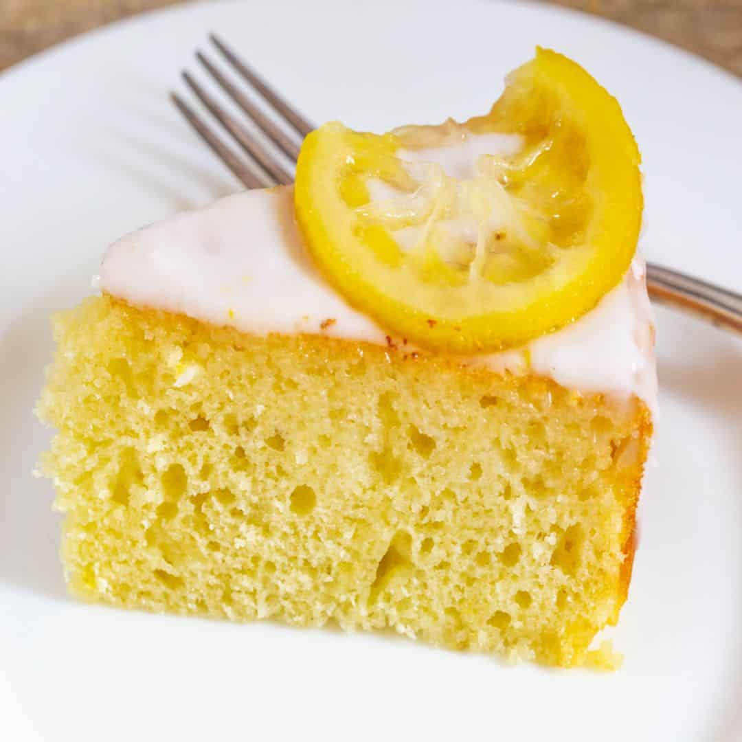 Light and moist yogurt cake with a lemon wedge on a white plate.