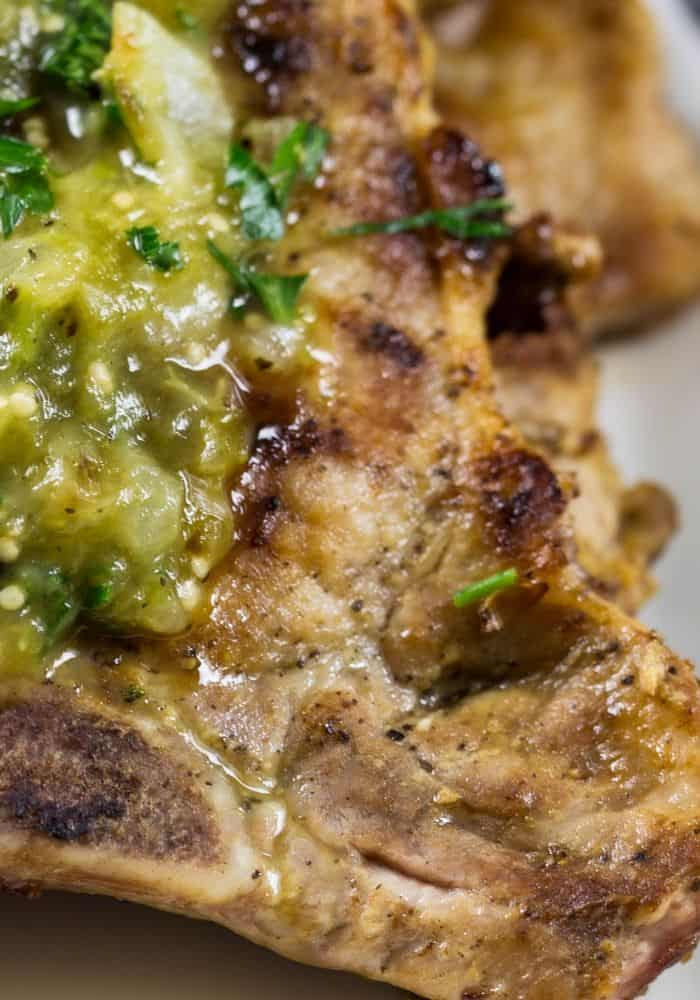 mexican pork chops that have been grilled and topped with tomatillo salsa\