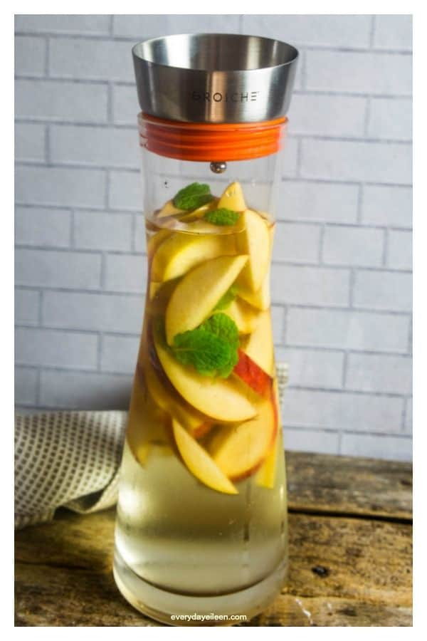 Refreshing peach sangria in a tall pitcher with fresh peach slices.