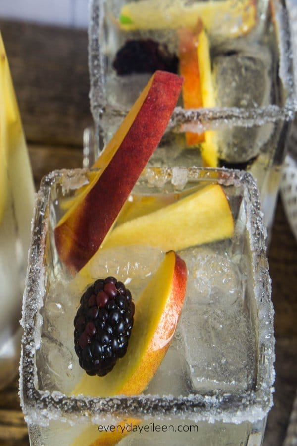 Peach sangria in a square glass rimmed with sugar, with ice cubes, sangria, peaches and blackberries.