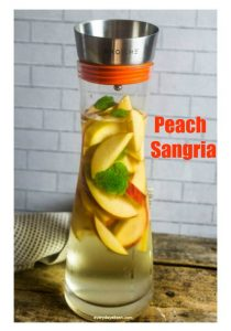Peach Sangria in a Grosche Sangria pitcher filled with sangria and peaches.