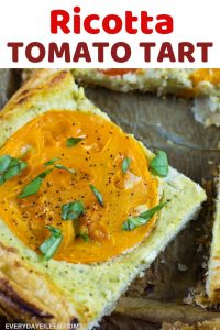 a tasty slice of ricotta tomato tart on a dark platter.
