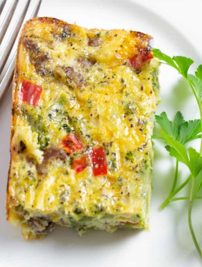 A delicious egg bake made with eggs, sausage, broccoli, peppers, and cheese on a white plate with a fork and a sprig of parsley on the plate.