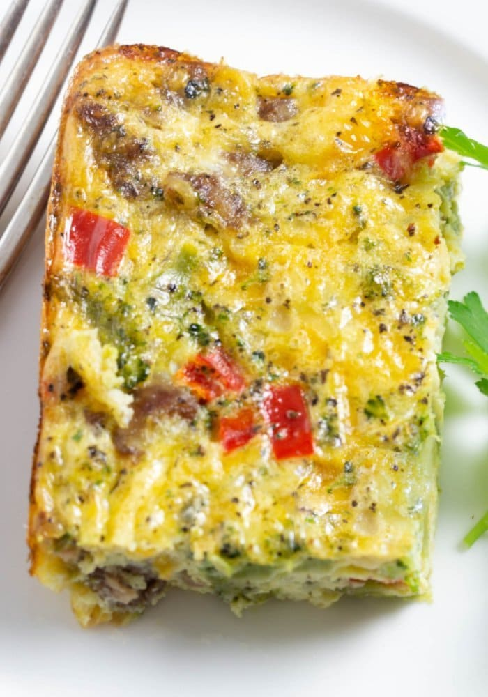 A delicious sausage and egg casserole filled with veggies and cheese on a white plate with fresh parsley.