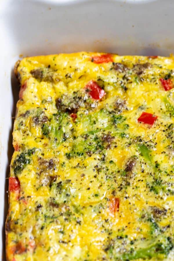 A breakfast casserole made with eggs, sausages, cheese and veggies in a casserole pan.