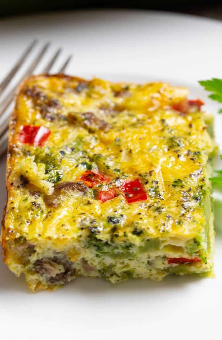 A delicious slice of an egg casserole on a white plate.