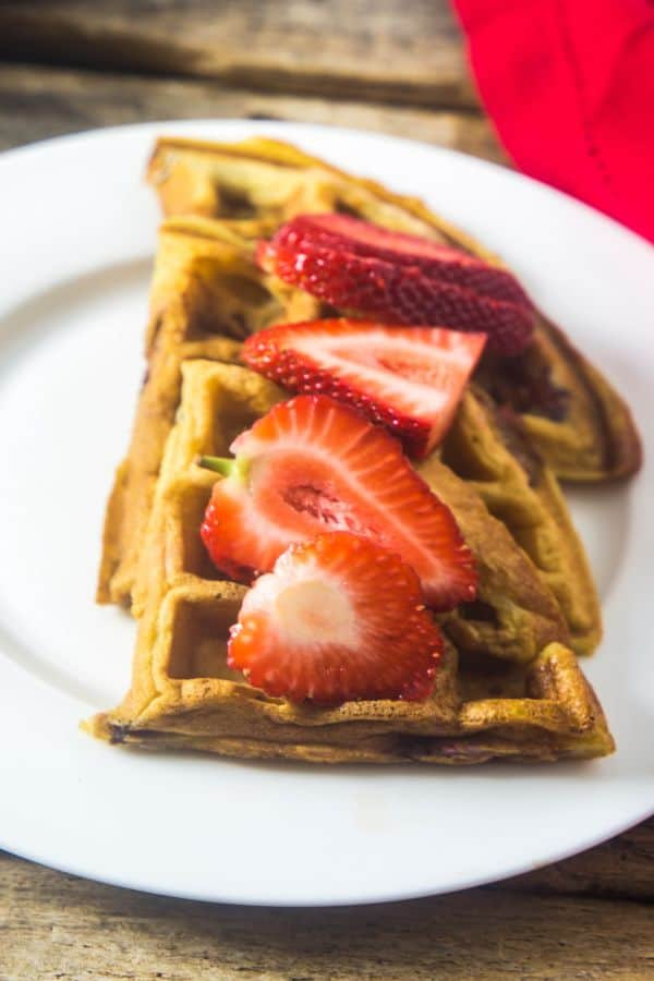 Strawberry waffles stacked on a plate with sliced strawberries on the waffles.