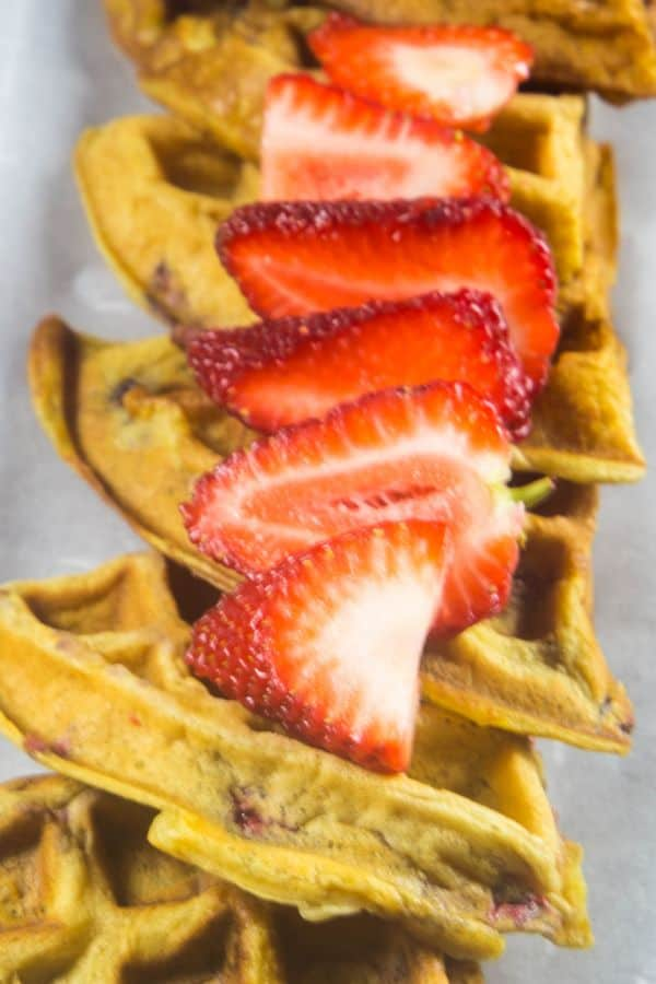 Strawberry waffles topped with fresh cut strawberries.