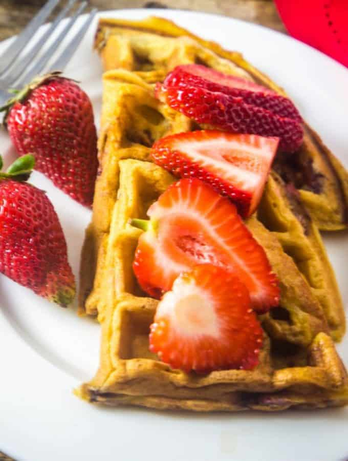 Strawberry waffles on a white plate with fresh strawberries drizzled over the waffles.