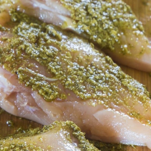 chicken breasts covered in homemade skinny basil pesto from everyday eileen ready to be grilled