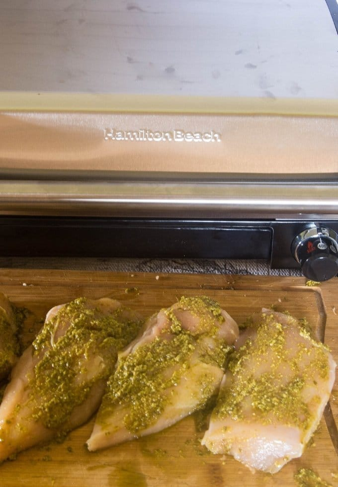 Boneless chicken breasts rubbed with Skinny Basil Pesto Sauce ready to be grilled on the hamilton Beach indoor grill