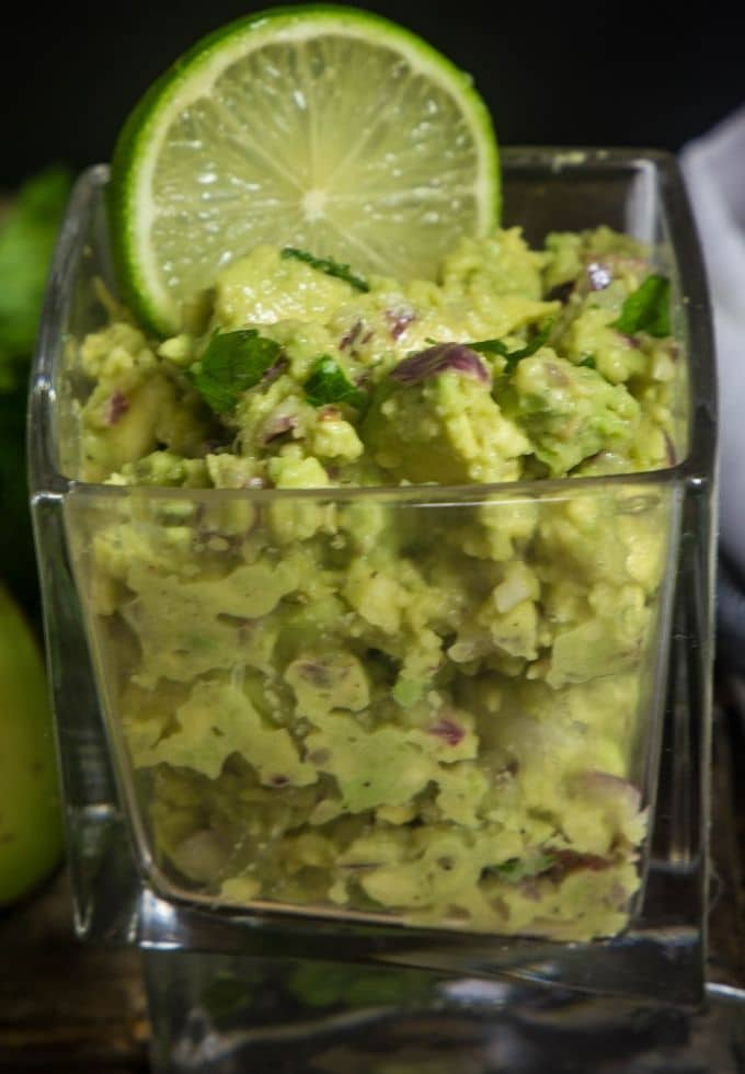fresh guacamole with cilantro and lime in a clear glass and lime wedge.