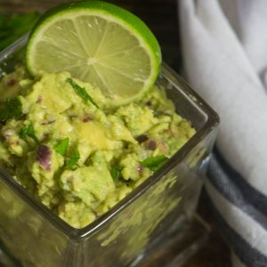 homemade guacamole in a glass jar with a lime wedge in the guacamole.