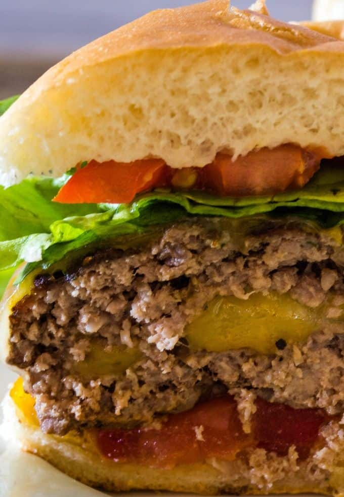 A delicious juicy lucy burger sliced in half and the melting cheese in the center is oozing out of the burger