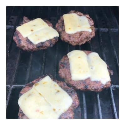 Burgers topped with pepper jack cheese on the grill to make taco burgers
