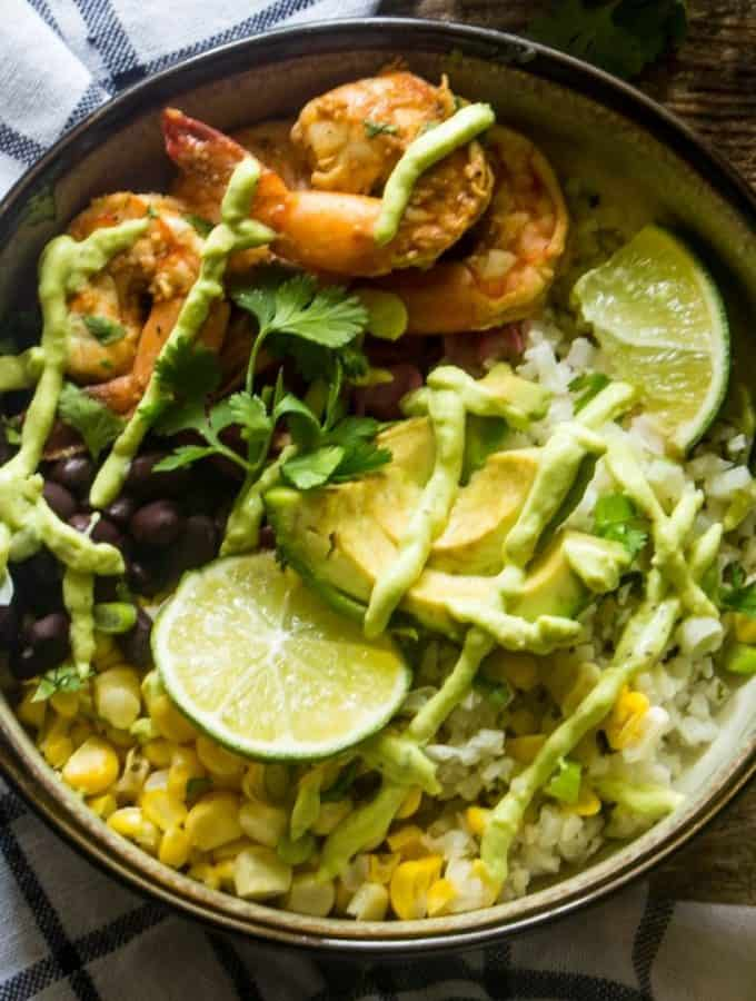 Delicious Baja Shrimp Bowl with cauliflower rice, corn, cabbage and avocado yogurt sauce