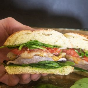 A grilled portobello mushroom burger sliced and topped with spinach, tomato, and cheese.