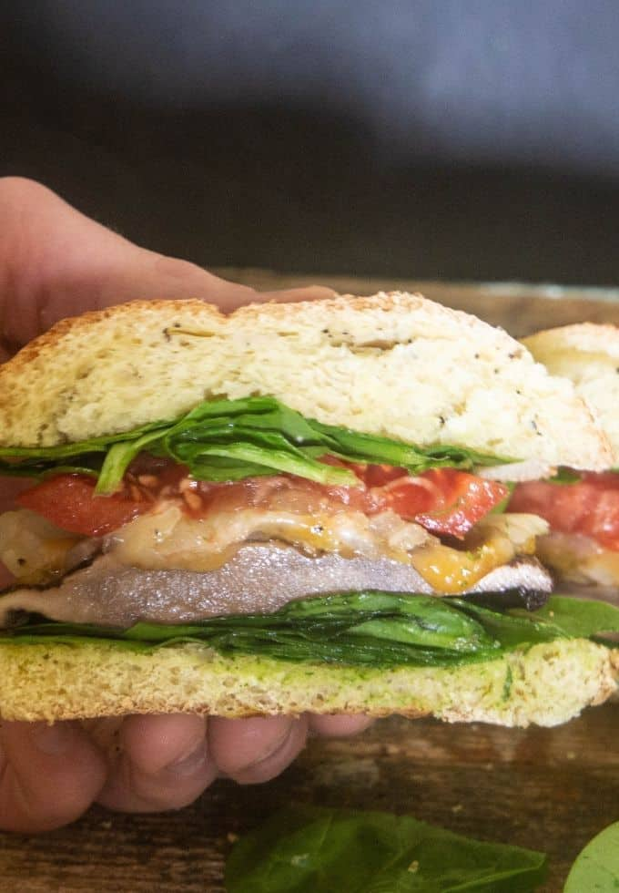 A grilled portobello mushroom burger sliced in half with lettuce, tomato, and cheese.