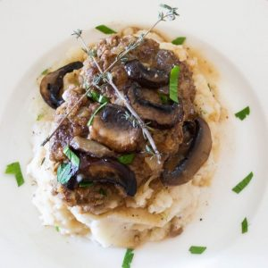hamburger steaks topped with mushrooms and brown gravy on mashed potatoes