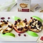 Apple slices topped with peanut butter, almonds, dried cranberries on a white platter