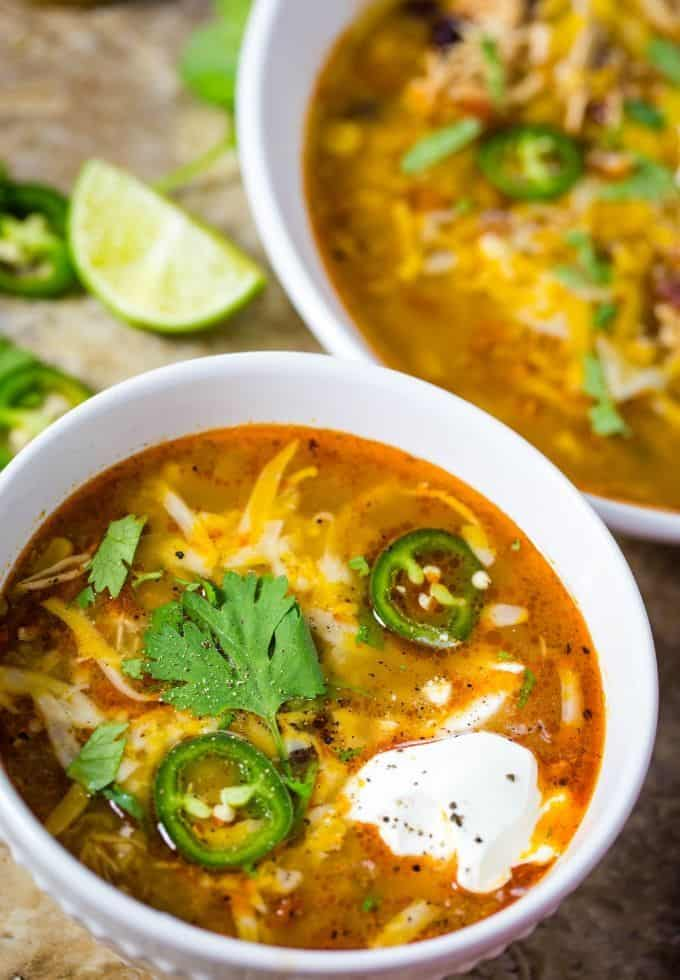 Slow cooker chicken soup in a white bowl topped with shredded cheese, jalapenos, and cilantro.