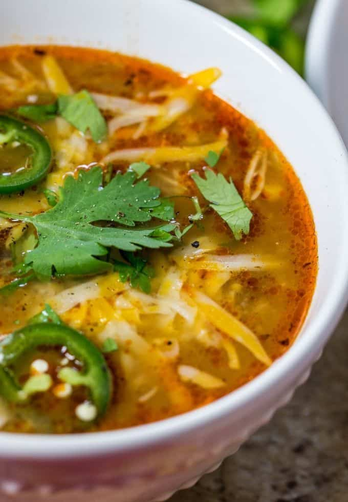 Enchilada soup topped with fresh cilantro, fresh jalapeno slices and shredded cheese.