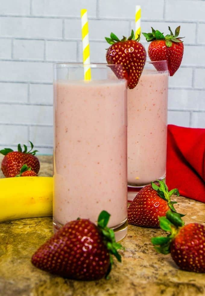 Refreshing strawberry banana smoothie in tall glasses with yellow straws and strawberries as garnish.