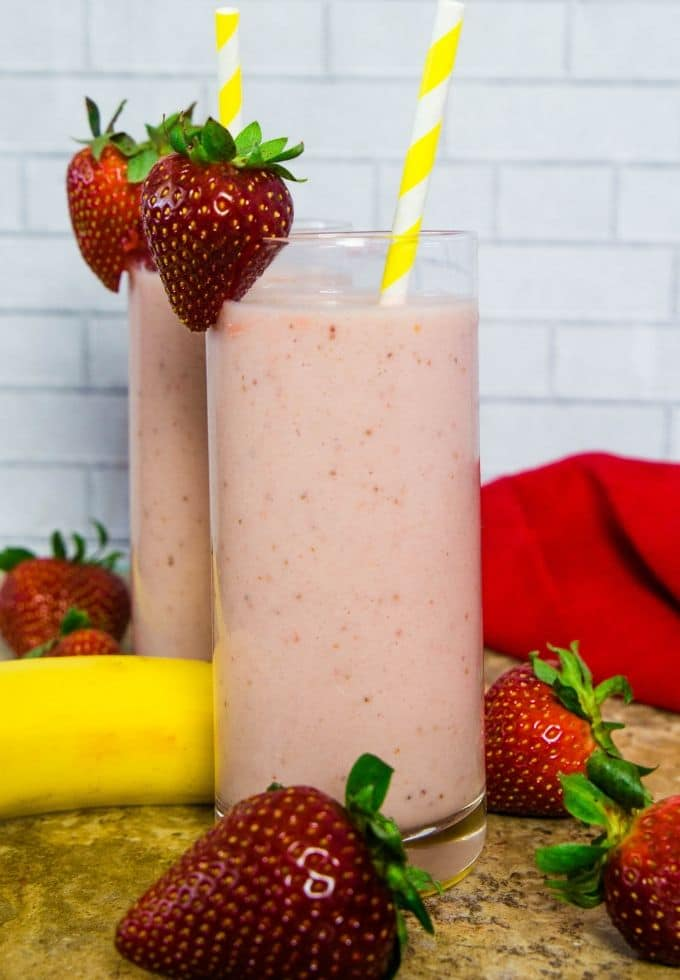 tall clear glass filled with strawberry banana smoothie topped with fresh strawberries and a yellow paper straw