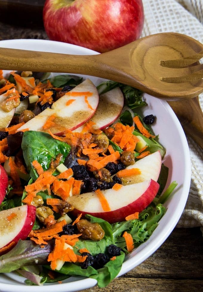 a large white salad bowl filled with apple walnut salad