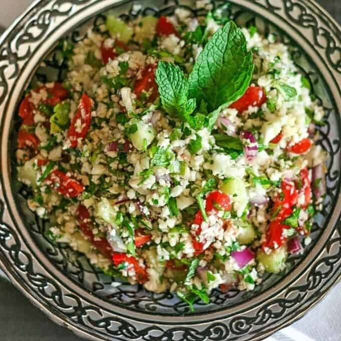 a delicious bowl of cauliflower tabbouleh with a vinaigrette and mint leaf in a silver bowl