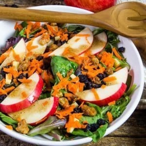 a delicious apple salad sprinkled with grated carrots in a white salad bowl.