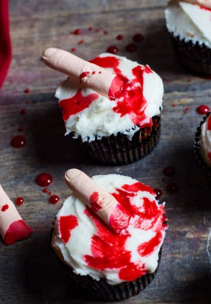 Halloween cupcakes with edible blood and edible fingers in aa vanilla cupcake