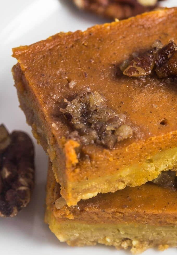 Sliced pumpkin bars on a platter with pecans