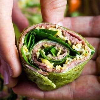 Roast beef tortilla rollups cut and being held in a hand