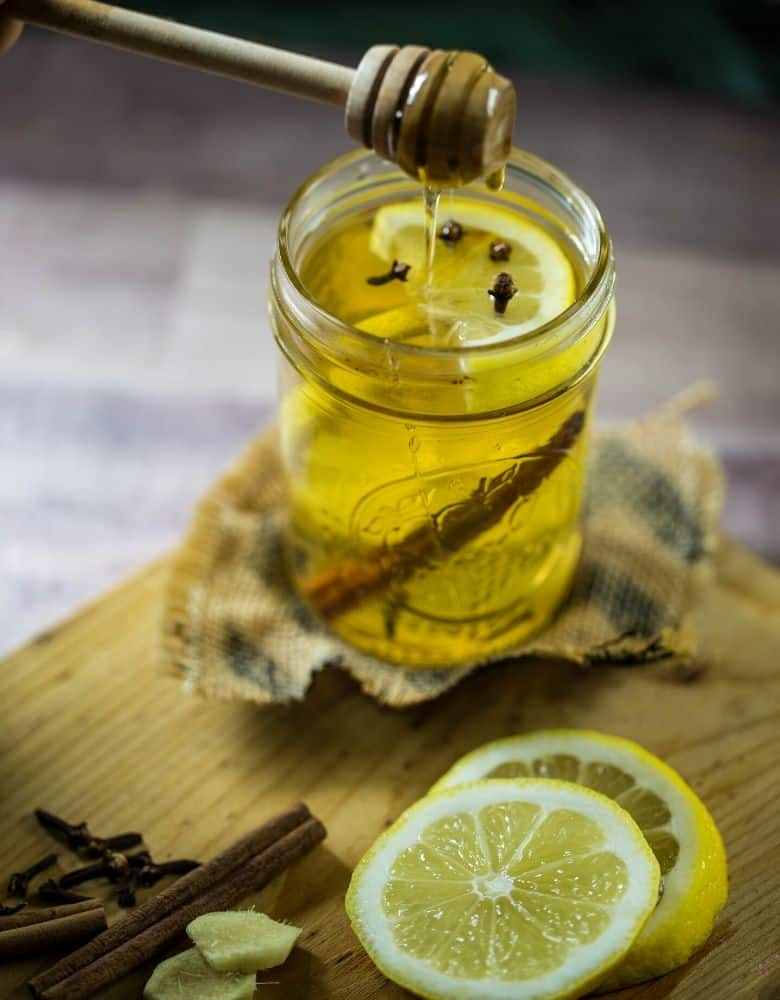 A mason jar filled with warm whiskey, lemon and cloves